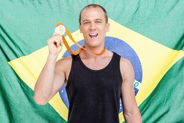 Athlete showing his gold medal in front of brazilian flag