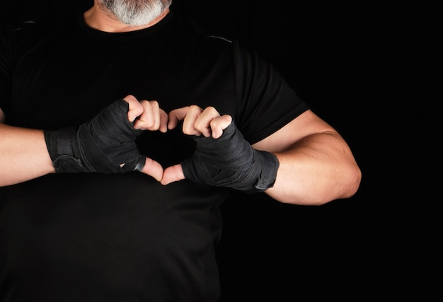 Athlete shows the symbol of the heart, the palm of a man is wrapped in a black sports bandage