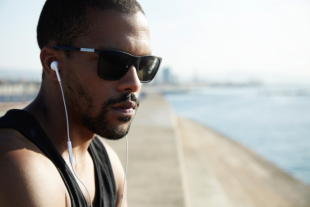 Athlete sitting on embankment on sunny summer day while resting after intensive training outdoors. exhausted fit runner resting at seaside after workout. sportsman listening to music with headphones