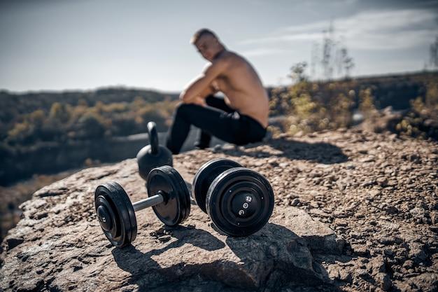 岩の上に座っている運動選手。自然の風景。フロントビューのダンベル。背景がぼやけている。