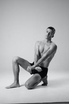 ショートパンツで屋内の床に座っているアスリートとボディービルダーの裸の胴体の白黒写真