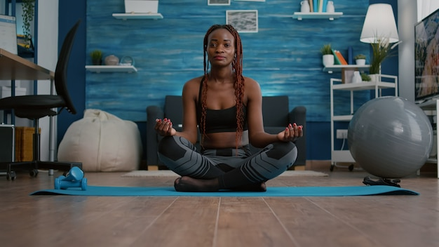 Athlete slim woman with dark skin putting in lotus position on yoga map
