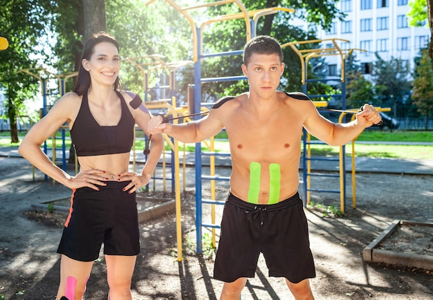 Athlete smiling brunette young female instructor helping handsome man wearing shorts with kinesiology elastic taping on body training arms using resistance rope at sports ground.