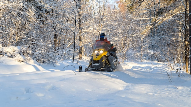 Athlete on a snowmobile in the winter forest.