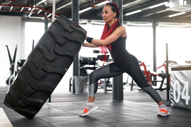 Athlete sportive woman lift wheel gym
