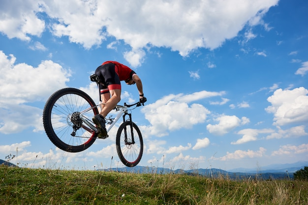 Athlete sportsman biker in professional sportswear flying in air on his cross country bike