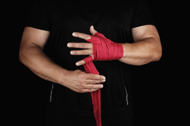Athlete stand in black clothes and wrap his hands in red textile elastic bandage before training