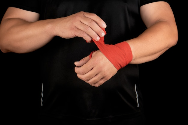 Athlete stand in black clothes and wrap his hands in red textile elastic bandage