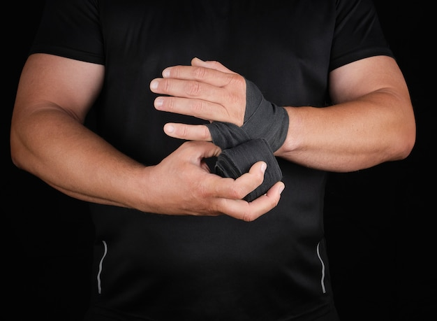 Athlete stand in black clothes and wrap his hands in textile elastic bandage