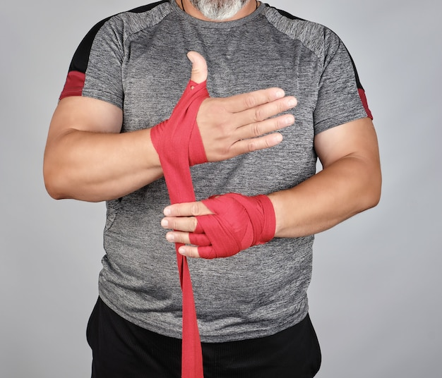 Athlete stand in gray clothes and wrap his hands in red textile elastic bandage