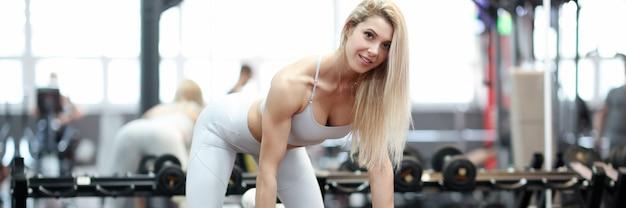 Спортсмен стоит в стойке на тренажере и держит концепцию программы тренировки гантелей и гантелей