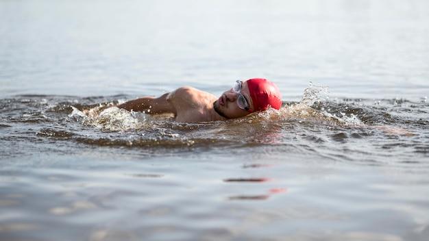 Спортсмен купается в озере