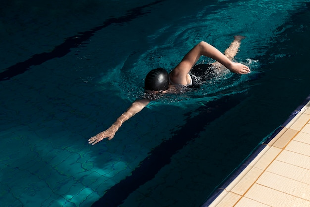 Athlete swimming in pool full shot