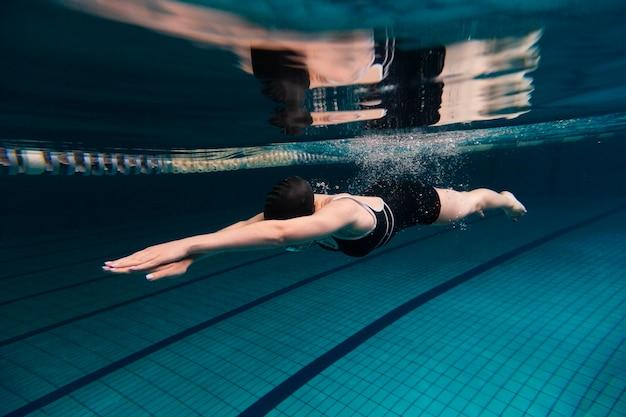 Athlete swimming underwater full shot