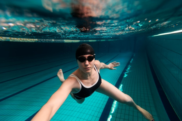 Athlete swimming with goggles full shot