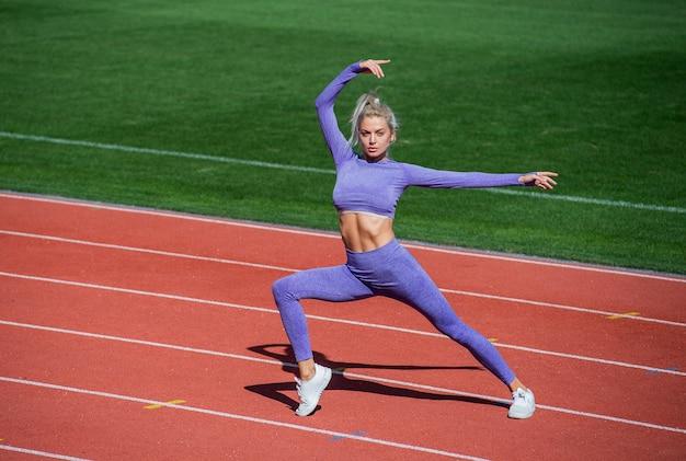 선수 워밍업입니다. 야외 경기장에서 워밍업. 훈련과 운동. 체육 여성 코치. 여성 스포츠 트레이너. 건강한 스포츠 라이프 스타일. 건강과 에너지. 피트 니스 운동복에 스트레칭 하는 여자.