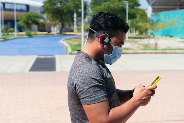 보호 마스크를 쓴 운동선수는 공원에 서서 휴대전화를 들고 헤드폰으로 음악을 들으며