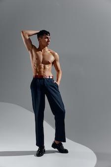 ポンプアップされた胴体裸の胴体ボディービルダーフィットネスジーンズの靴を履いたアスリート