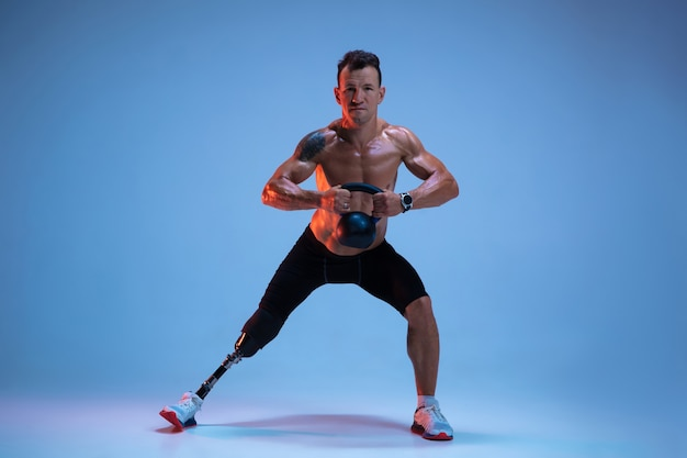 Athlete with disabilities or amputee isolated on blue studio background. professional male sportsman with leg prosthesis training with weights in neon.