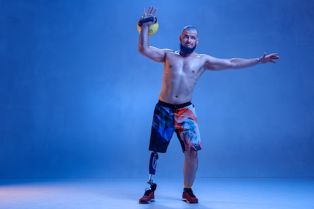 Athlete with disabilities or amputee isolated on blue studio wall