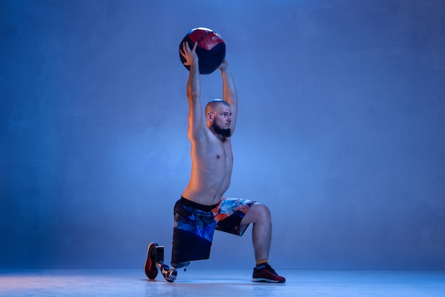 Atleta con disabilità o amputato isolato sulla parete blu. sportivo maschio professionista con allenamento di protesi di gamba con palla al neon. sport per disabili e superamento, concetto di benessere.