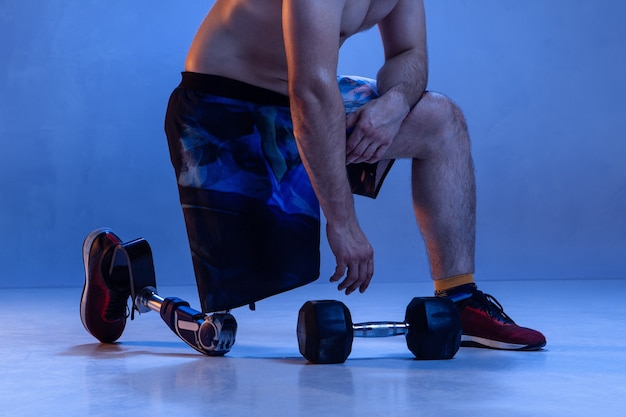 Athlete with disabilities or amputee isolated on blue wall. professional male sportsman with leg prosthesis training with weights in neon. disabled sport and overcoming, wellness concept.