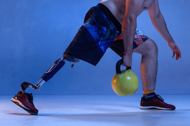 Athlete with disabilities or amputee isolated on blue wall.