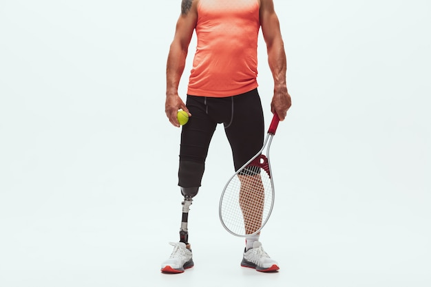 Athlete with disabilities or amputee isolated on white. professional male tennis player with leg prosthesis training