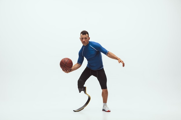 Athlete with disabilities or amputee isolated on white studio space. professional male basketball player with leg prosthesis training and practicing in studio.