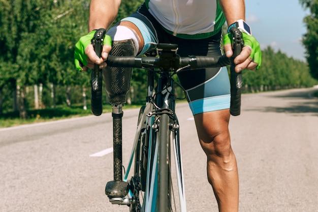 Atleta con disabilità o amputato che si allena in bicicletta nella soleggiata giornata estiva. sportivo maschio professionista con protesi della gamba che praticano all'aperto. sport per disabili e concetto di stile di vita sano.