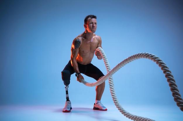 障害者または切断患者の青のスタジオの背景に分離された運動選手。ネオンの重みで脚義足トレーニングとプロの男性スポーツマン。