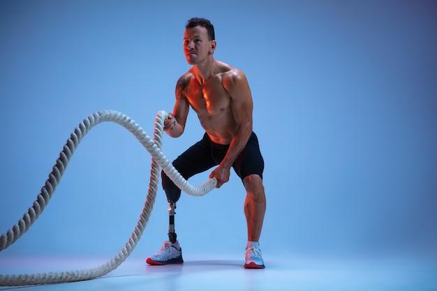 青いスタジオの背景に孤立した障害のある運動選手または切断者