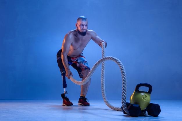 파란색 스튜디오 벽에 격리된 장애 또는 절단 장애인 선수