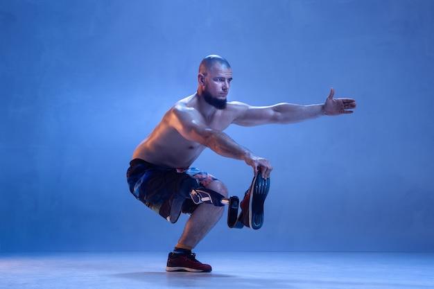 青い壁に孤立した障害のある運動選手または切断者。ネオンで活躍する義足のトレーニングを受けたプロの男性スポーツマン。障害者スポーツと克服、ウェルネスの概念。