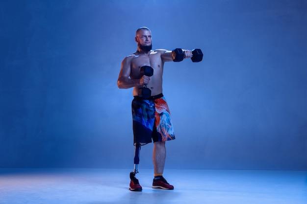 青い壁に孤立した障害のある運動選手または切断者。ネオンでウェイトトレーニングをしている義足のプロの男性スポーツマン。障害者スポーツと克服、ウェルネスの概念。