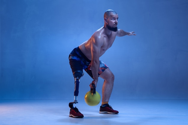 장애 또는 수족이 파란색 벽에 고립 된 선수. 네온의 무게로 다리 보철물 훈련을하는 전문 남성 운동가. 장애인 스포츠 및 극복, 웰빙 개념.