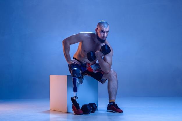 Спортсмен-инвалид или человек с ампутированной конечностью, изолированные на синей стене.