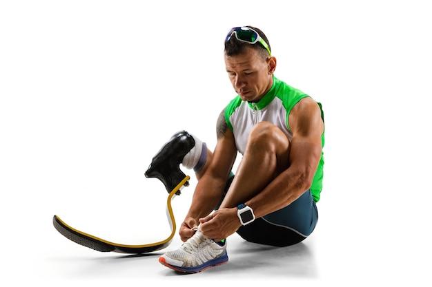 白いスタジオの背景に孤立した障害のある運動選手または切断者。義足のトレーニングとスタジオでの練習を行うプロの男性ランナー。障害者スポーツと健康的なライフスタイルの概念。