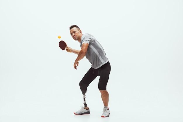 Спортсмен с ограниченными возможностями или инвалидом, изолированные на белом фоне студии. профессиональный игрок в настольный теннис с протезированием ноги тренируется в студии. концепция спорта и здорового образа жизни для инвалидов.