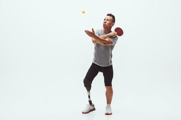흰색 스튜디오 배경에 격리된 장애 또는 절단 장애인 운동선수. 스튜디오에서 다리 의족 훈련을 받은 전문 남성 탁구 선수. 장애인 스포츠와 건강한 생활 방식 개념.