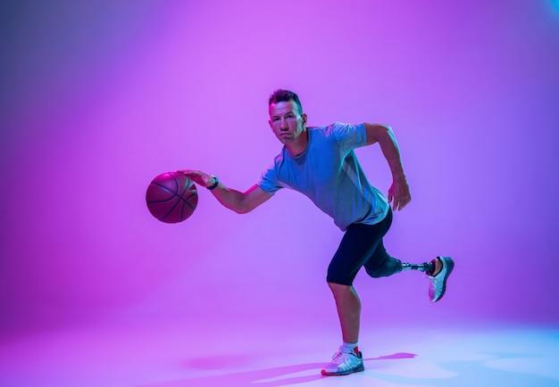 障害を持つアスリートまたはネオンのグラデーションスタジオの背景に切断者。バスケットボール選手