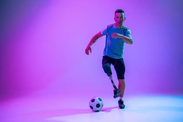 スタジオのバックグラウンドで障害のあるアスリートまたは切断者。サッカー選手