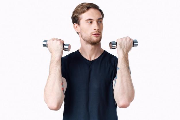그의 손과 검은 티셔츠 운동 피트니스 보디에 아령을 가진 선수. 고품질 사진