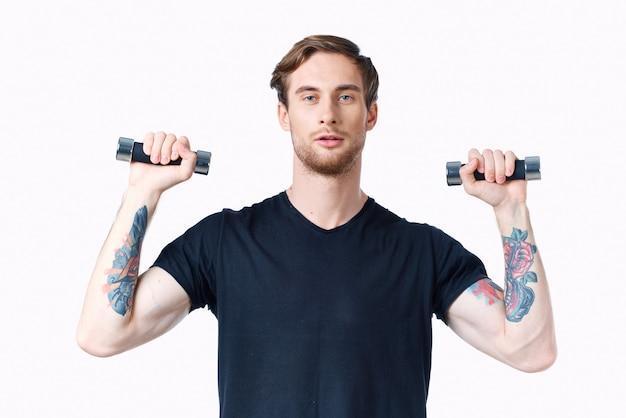 Спортсмен с гантелями в руках и в черной футболке делает упражнения фитнес культурист