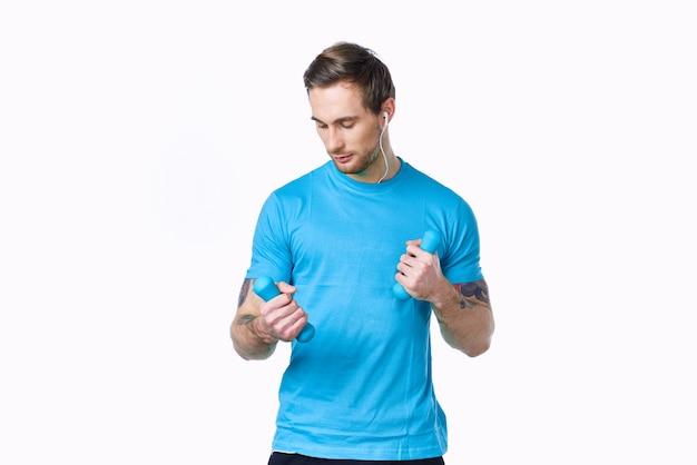 明るい背景と青いtシャツパンツのタトゥーにダンベルを持つアスリート。高品質の写真