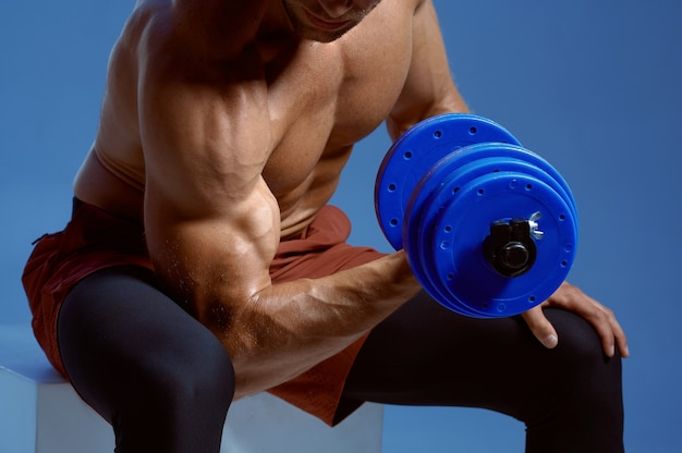 Athlete with dumbbells sitting on cube in studio
