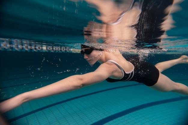 Спортсмен с очками плавает под водой