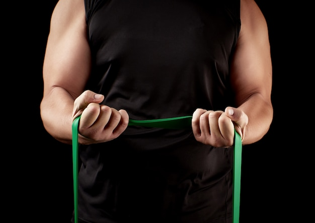 Athlete with a muscular body in black clothes doing physical exercises with green rubber