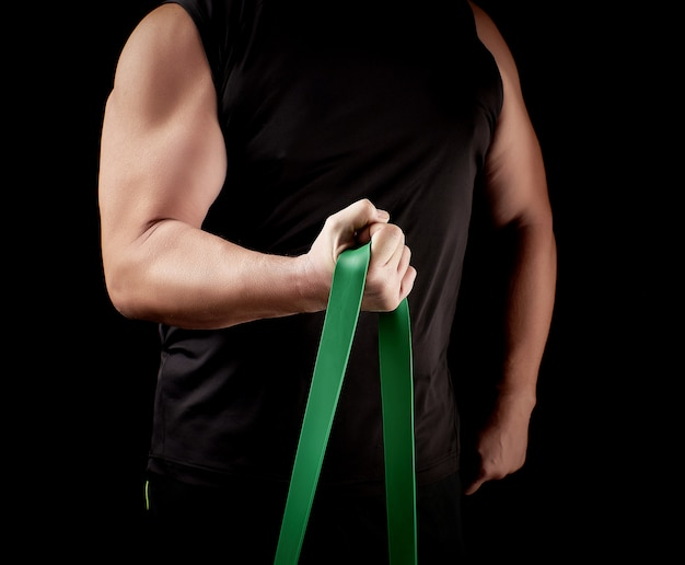 Athlete with a muscular body in black clothes is doing physical exercises with green rubber
