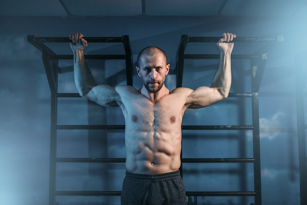 Athlete with muscular body training on horizontal bar in gym.